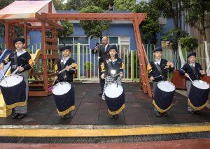 Niños uniformados tocando tambores